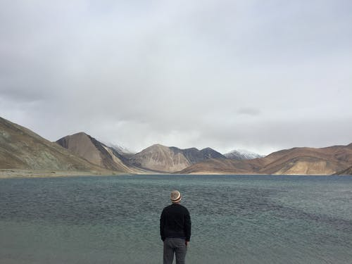 Person Standing Facing Body of Water With Hills at Distance
