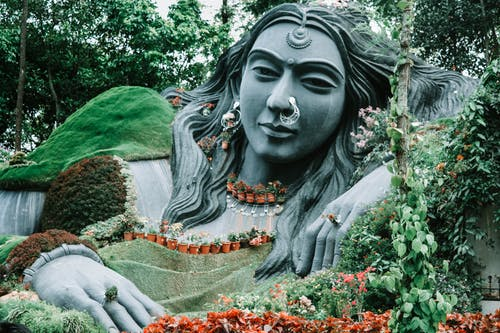 Gray Concrete Statue Surrounded by Green and Red Flowers