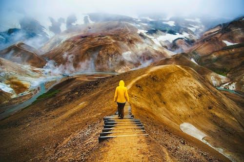 Gratis lagerfoto af bakker, bjerge, eventyr, gul jakke