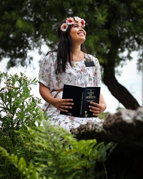 Woman Wearing White Floral Dress Holding Book