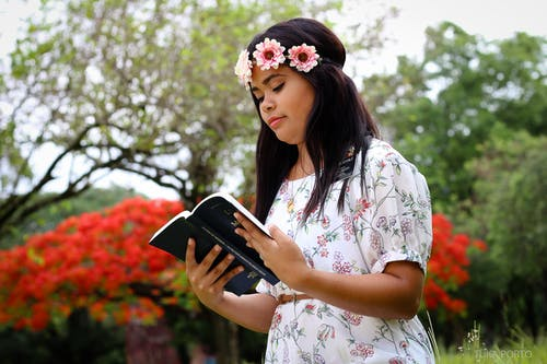 Photo of Woman Wearing White Floral Dress While Holding Book