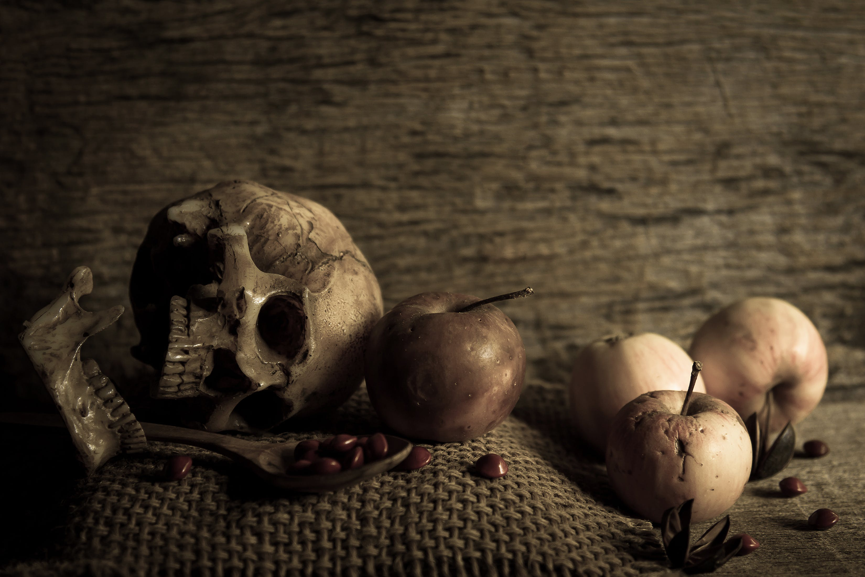 Broken Skull Beside Apples and Spoon