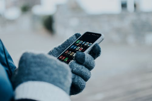 Person Wearing Gloves Holding a Cellphone