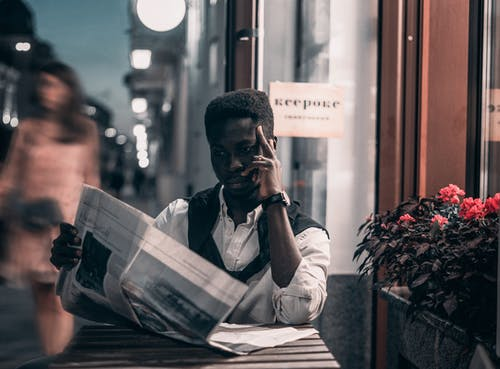 Черный мужчина читает газету