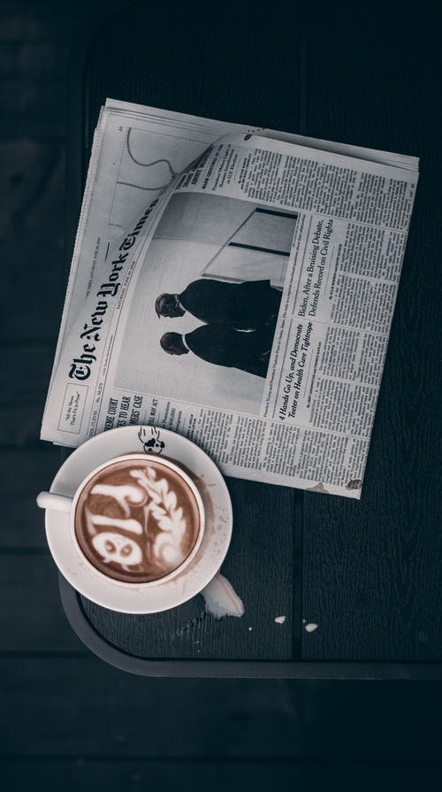 White Newspaper Beside Teacup