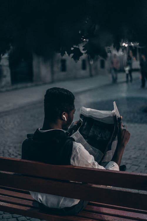 Man Reading a Newspaper Sitting on Wooden Bench