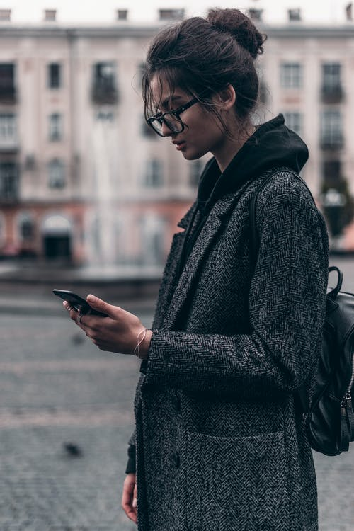 Woman in Gray and Black Coat Using Smartphone