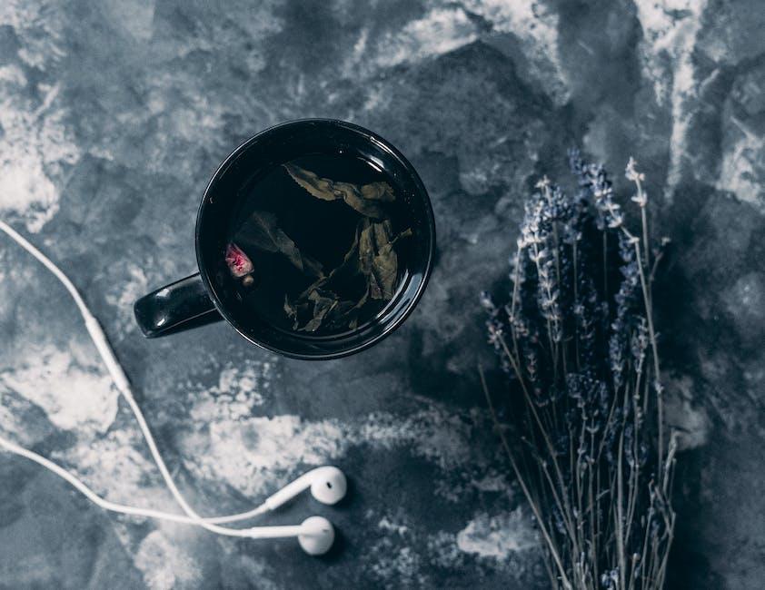 Tea in black ceramic mug near apple earpods