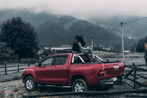 Two Women Sitting on Red Pickup Truck Viewing Mountain on a Foggy Day