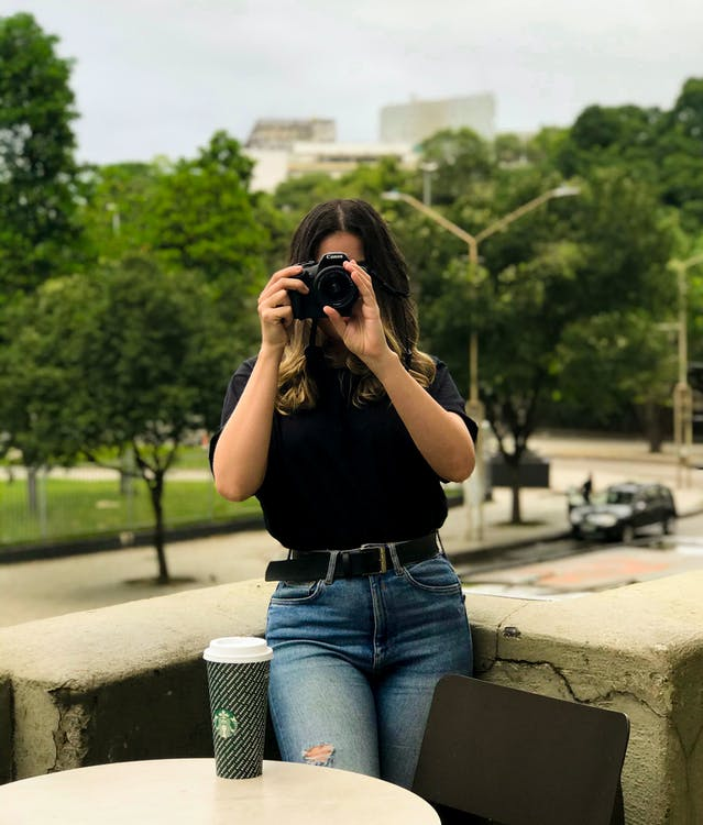 黒のデジタル一眼レフカメラを保持しながら黒のtシャツと青のデニムジーンズを着ている女性
