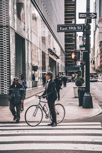 Shallow focus photo of man standing beside gray bike on crosswalk