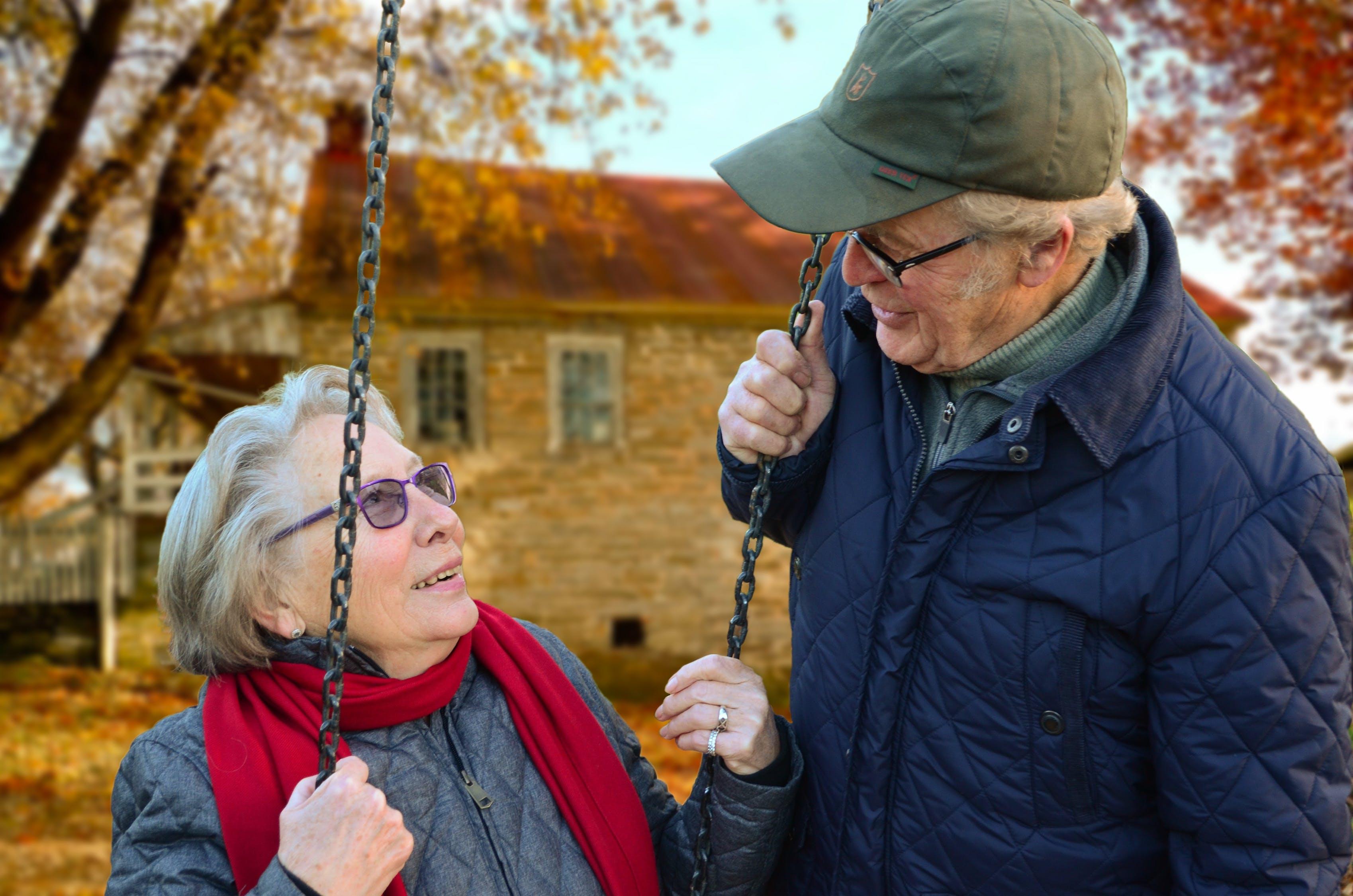 Man Standing Beside Woman on Swing