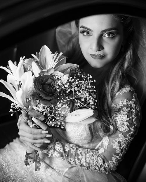 Grayscale Photography of Woman Carrying Flower Bouquet