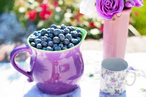 Black Berries on Purple Container Beside White and Purple Floral Mug