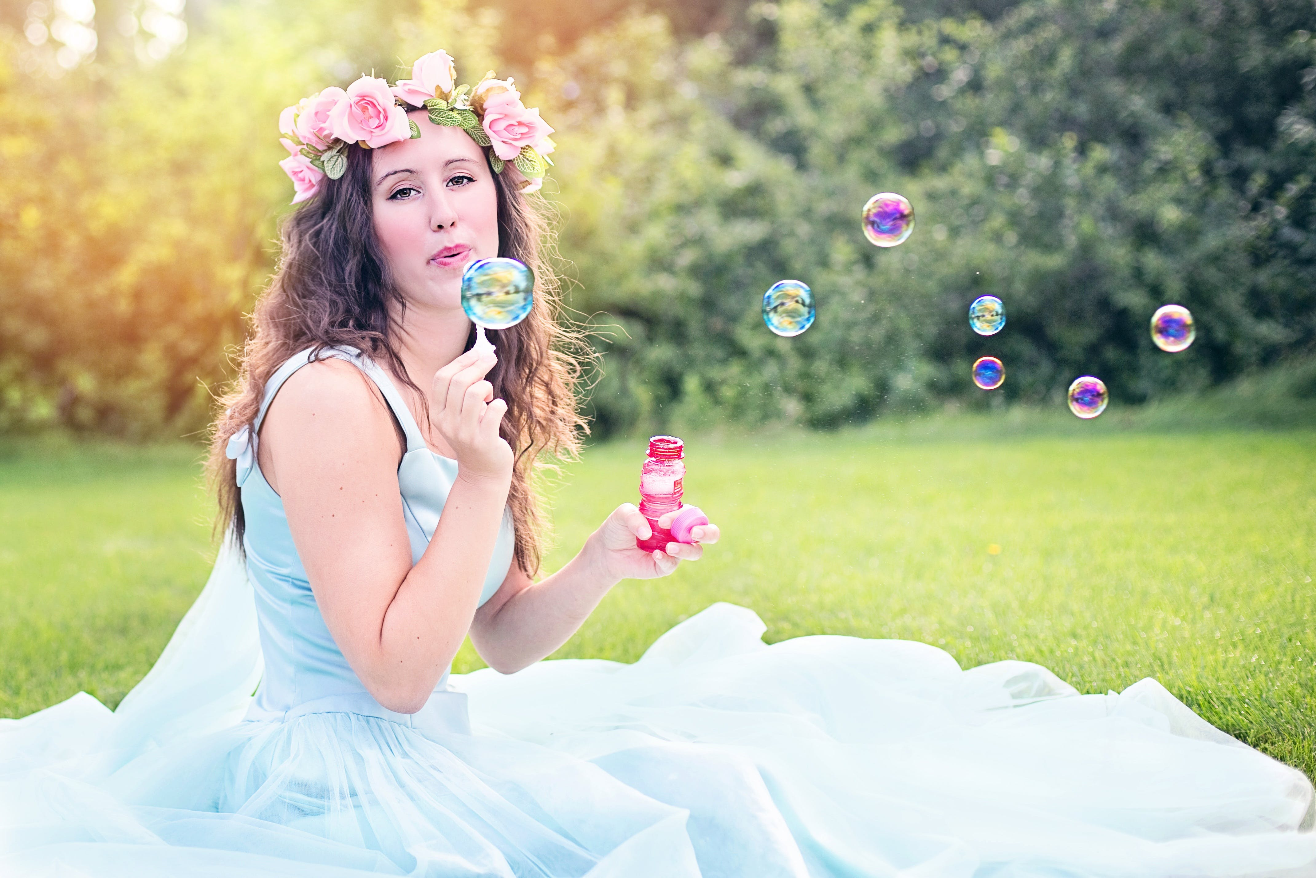 Woman Sitting on Grass Blowing Bubbles