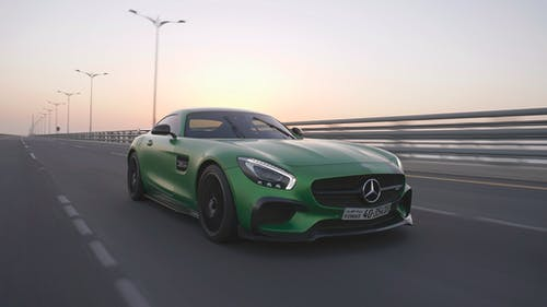 Green luxury car driving fast on asphalt road