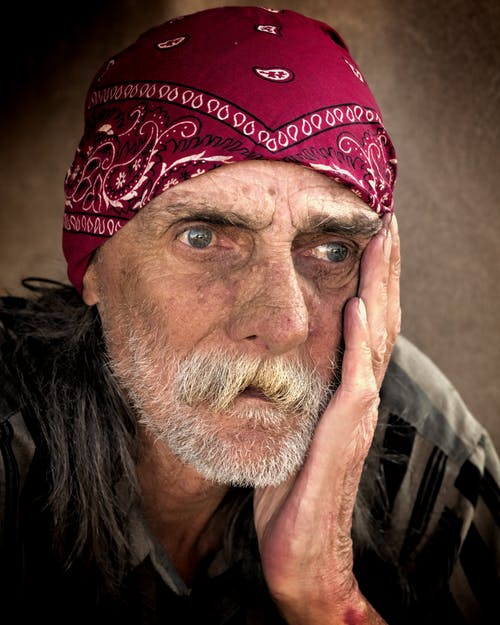 Man Wearing Red and Gray Paisley Bandana Holding His Cheek