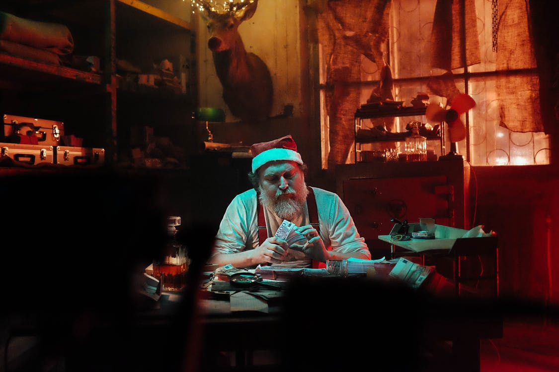 Man in Santa Hat Sitting on Chair Counting Money