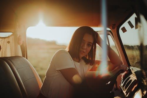 Photo of Woman Leaning on Steering Wheel