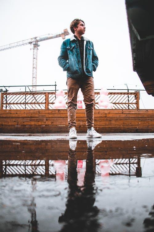 Man Wearing Blue Denim Jacket and Brown Pants