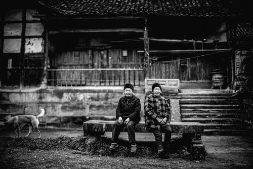 Grayscale Photo of Two People Sitting on Bench