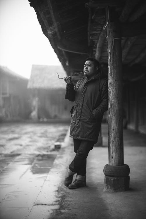 Grayscale Photography of Man Smoking Outdoors