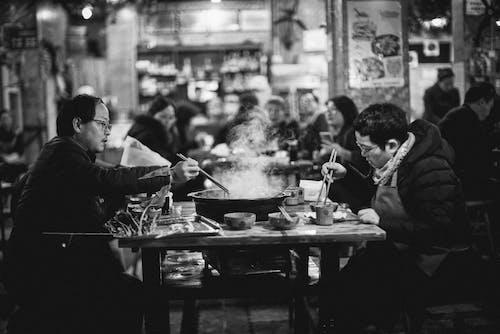Greyscale Photo of People Eating