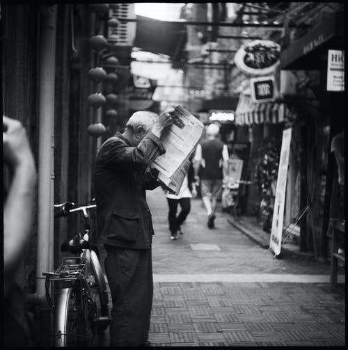 Grayscale Photo of Person Standing While Holding a Newspaper