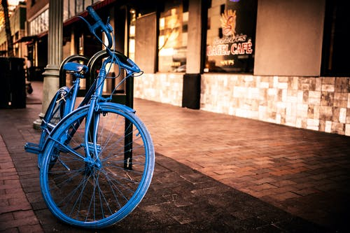 Blue City Bike Parked Beside Brown Brick Wall