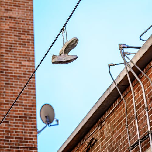 Low Angle Photo of Shoes Hanging on Wire