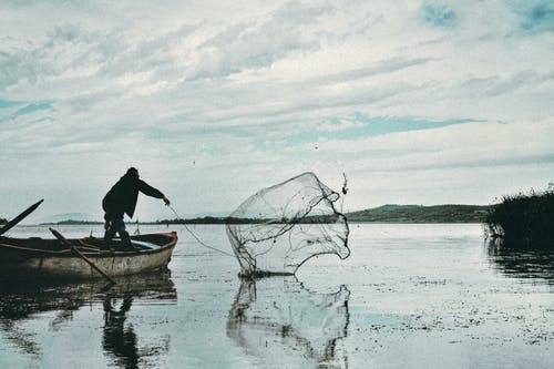 Man Casting His Net in the Body of Water