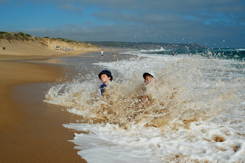 Two Men Crouching on Beach Shoreline