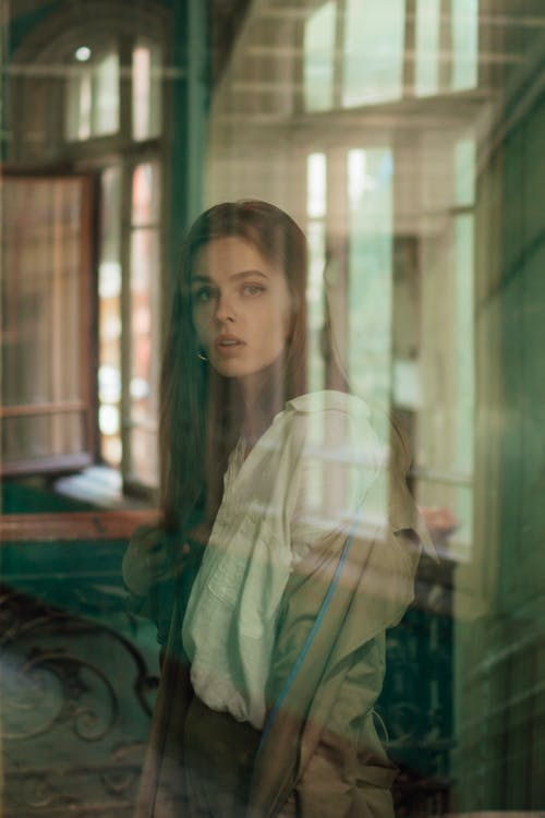 Woman in Brown Jacket and White Collared Button-up Shirt Facing A Glass Window