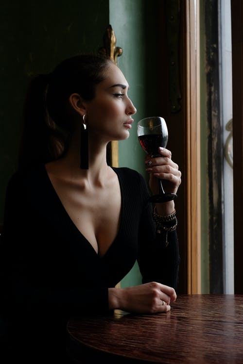 Woman Sitting on Chair Beside Table While Holding Wine Glass