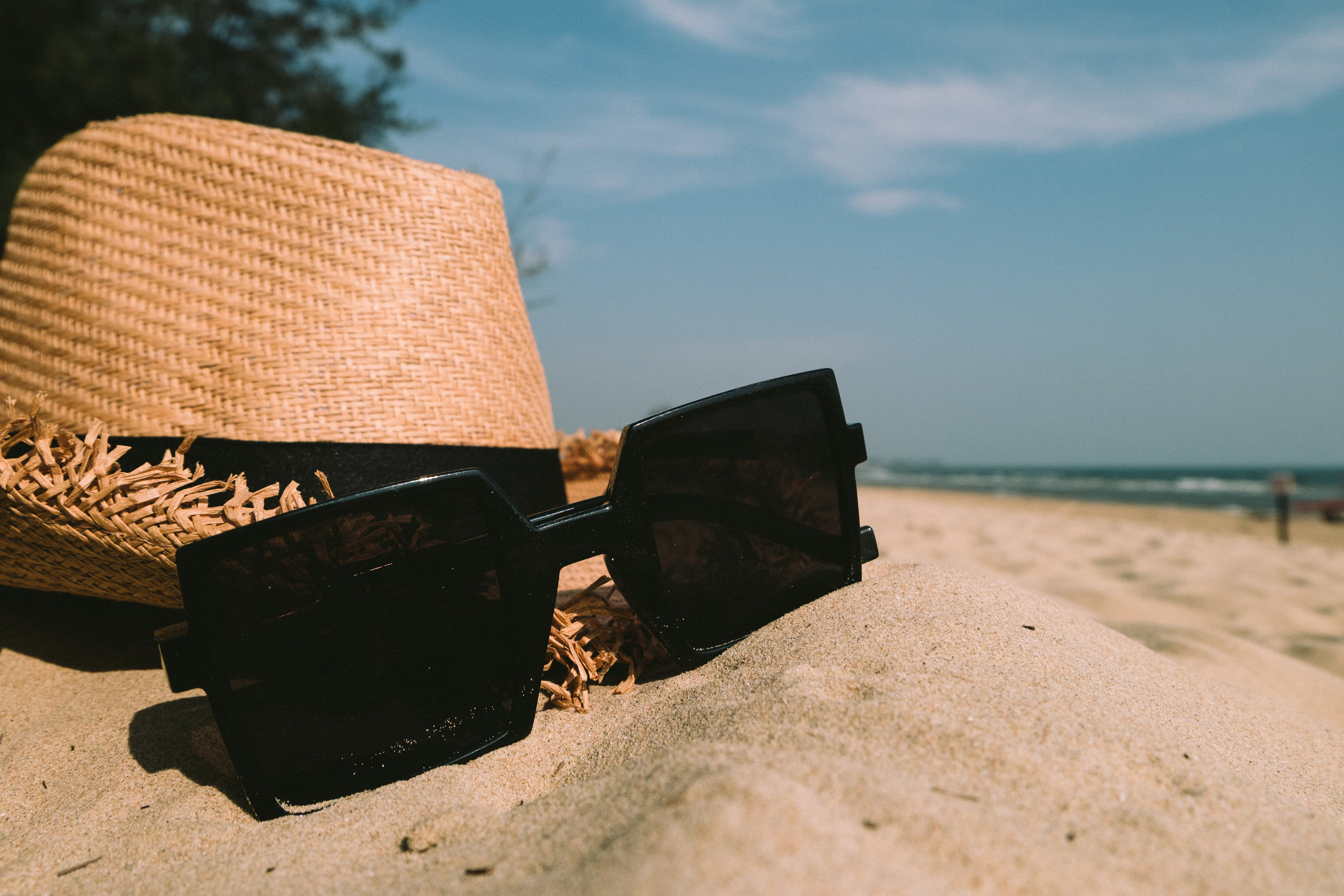 Sunglasses Beside Sun Hat on Sand