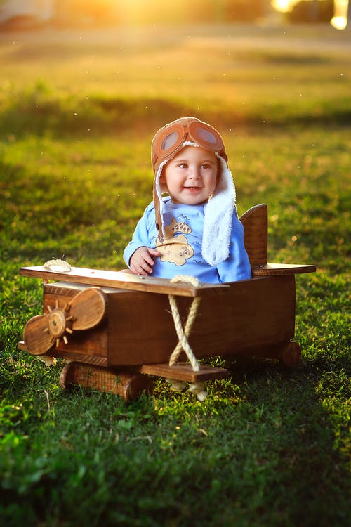 Photo of Baby Sitting on Wooden Airplane