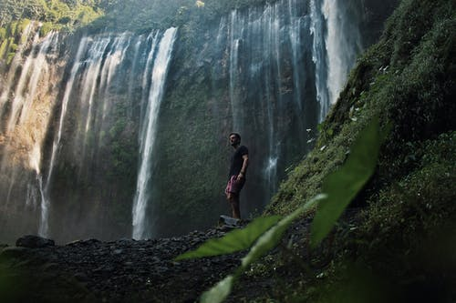 Photo Of Man Standing Near Falls