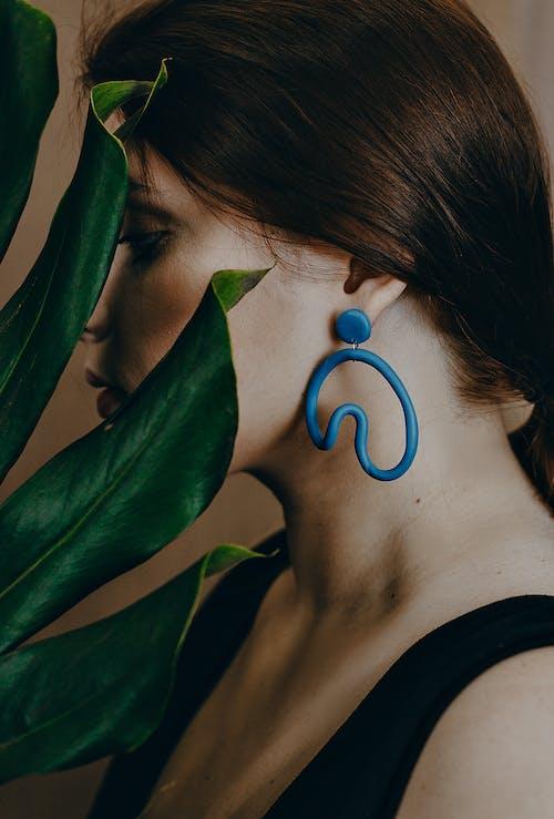 Photo of Woman Wearing Blue Earring Near Green Leaves