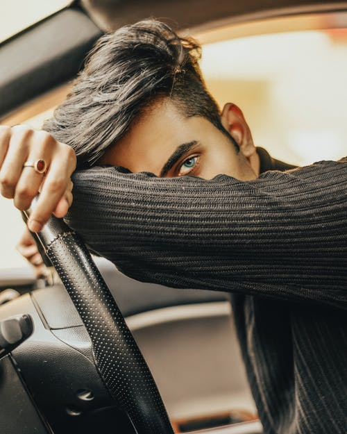 Man Leaning on Car Steering Wheel