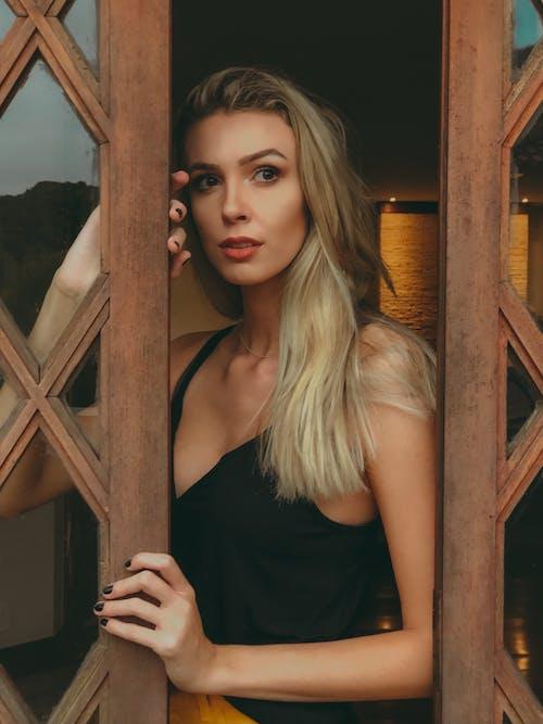 Woman Peeking on Brown Wooden Door