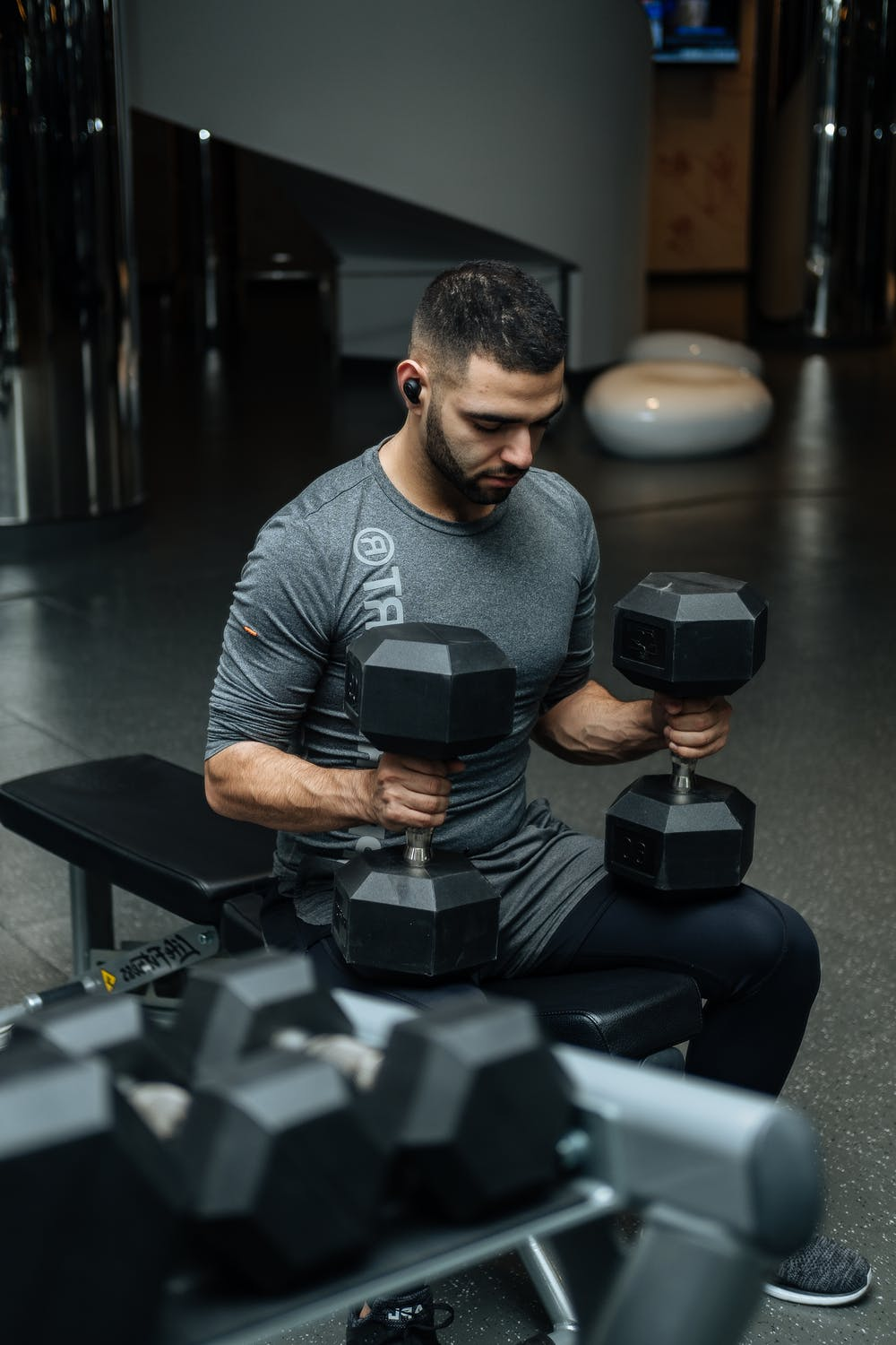 man sitting on workout bench with 2 dumbbells getting mentally prepared to lift