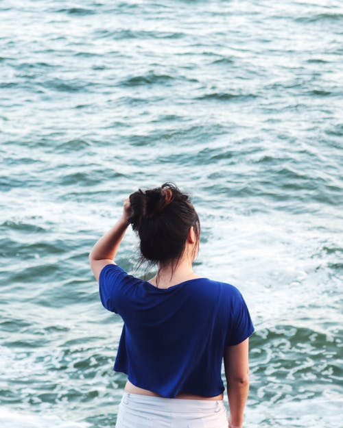 Woman in Blue Shirt Standing Near Body of Water