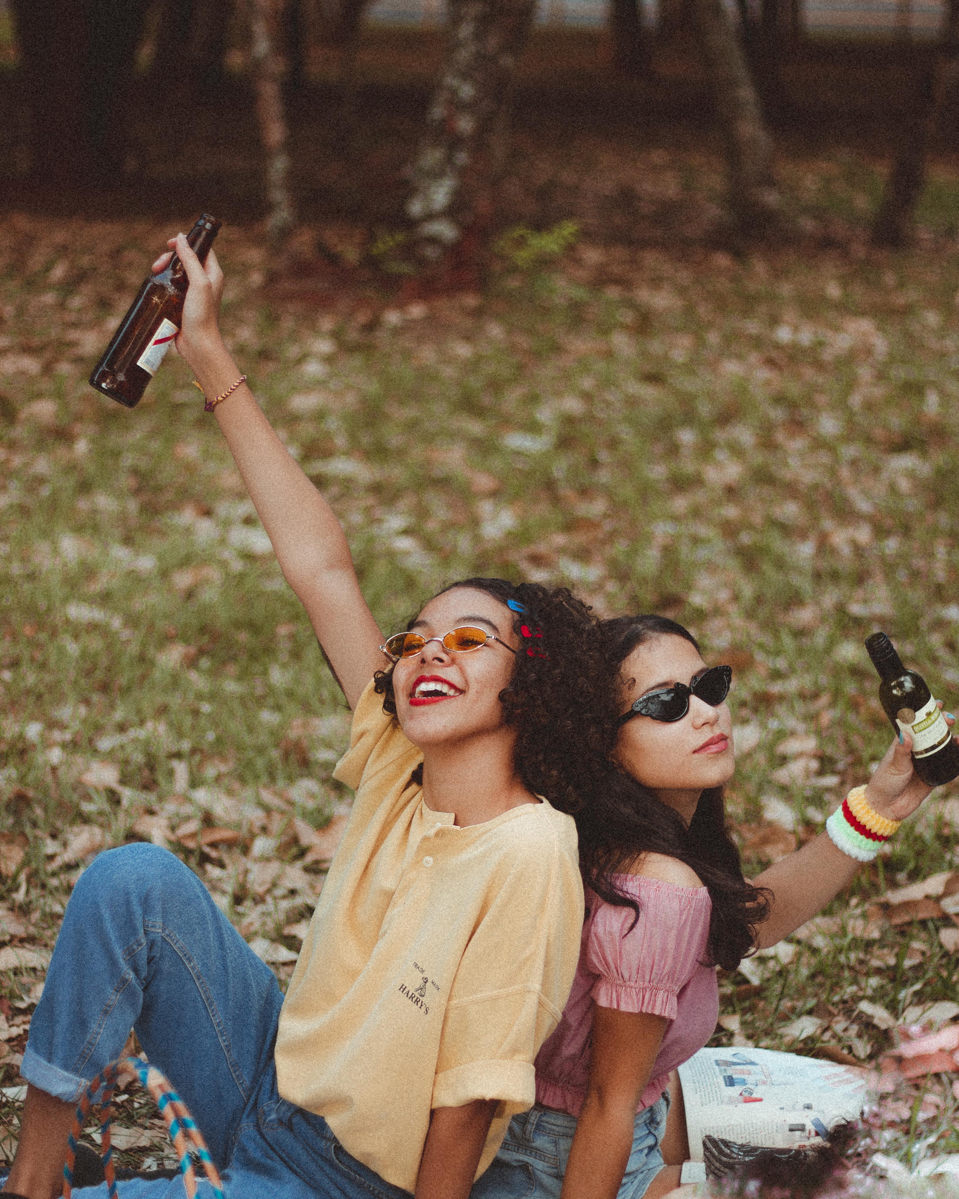 two smiling women holding bottle sitting on green grass field