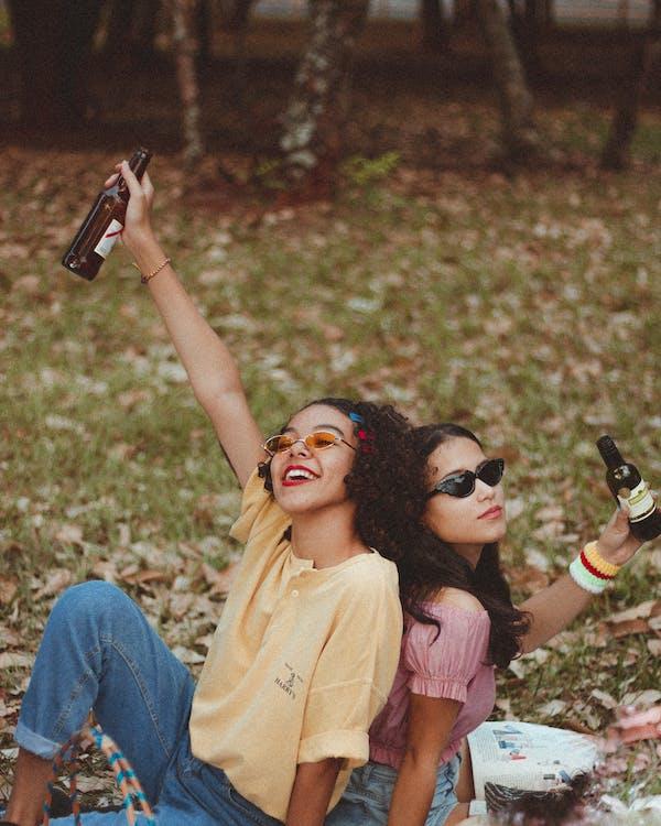 Dwie Uśmiechnięte Kobiety Trzymając Butelkę Siedzi Na Polu Zielonej Trawie