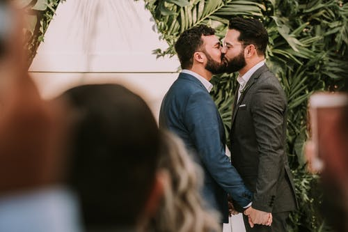 Men Wearing Suit Kissing in Front of People