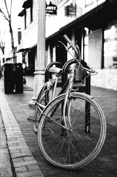 Grayscale Photo of Bicycle Parked on Sidewalk