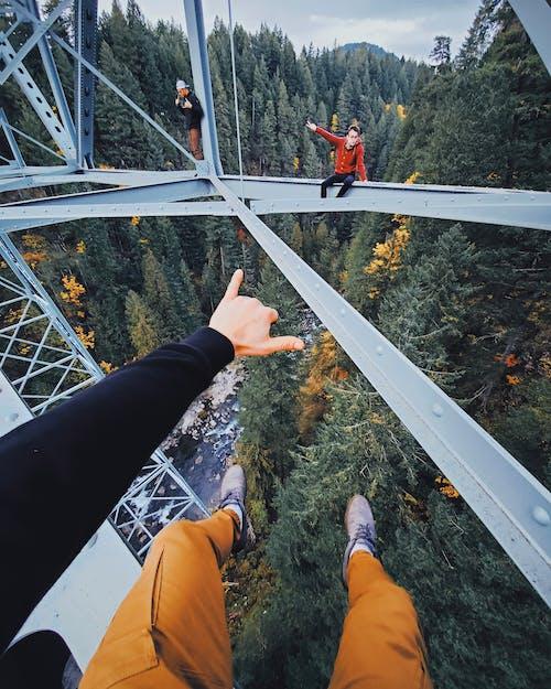 Persona In Pantaloni Neri E Scarpe Marroni In Piedi Sul Ponte Di Metallo Bianco