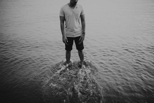 Man in White Crew Neck T-shirt and Black Shorts Standing on Water
