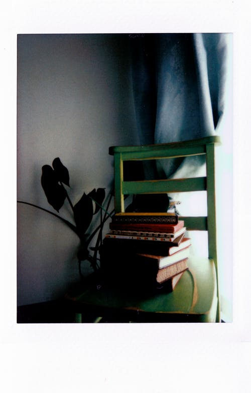 Assorted Books on Green Wooden Chair