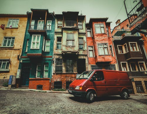 Red Van Parked Beside Brown and Green Concrete Building